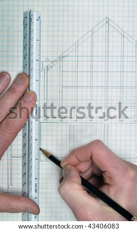 House floor plan from architect on grid paper with ruler and hands drawing the lines with a pencil. This makes a great background and has copyspace.