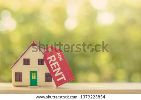 House for rent concept : Model house with a paper tag with chain, depicts a payment for temporary use of a property owned by another owner, tenant unwilling to pay full price, avoid burden of upkeep.