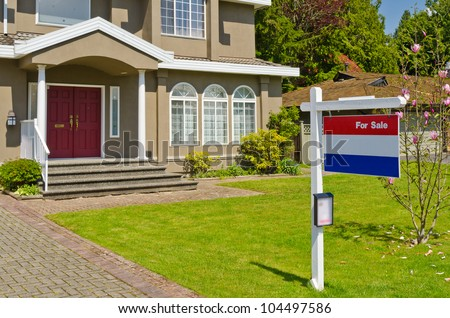 House For Sale Real Estate Sign in Front of New House. - stock photo