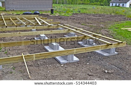 House framing. Floor beams on the foundation blocks for the construction of a summer house, a terrace or a summer cafe. Septic tank #514344403