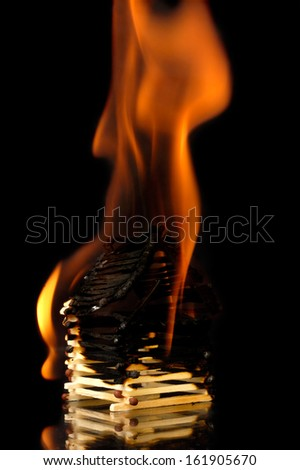 House from matches burning down with flames. Conceptual symbol isolated on black background