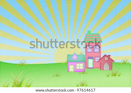 house from recycle paper with grass field and sun set background