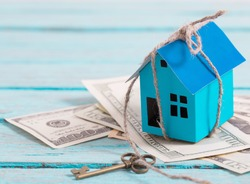 House from the paper and money on wooden background