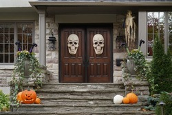 House front doors with Halloween skull decorations and pumpkins