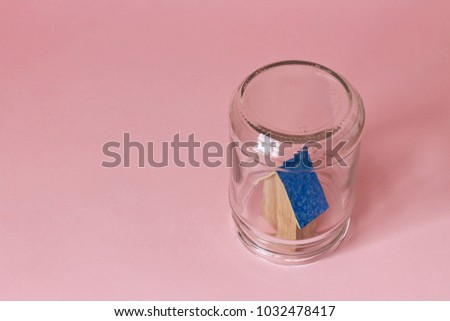 House in a jar protected in safety. Protected from misfortunes. House in a jar on a pink background with a blue roof. #1032478417