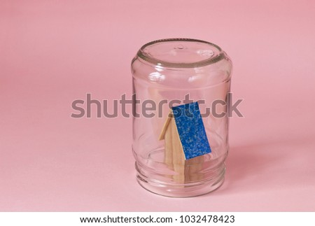 House in a jar protected in safety. Protected from misfortunes. House in a jar on a pink background with a blue roof. #1032478423