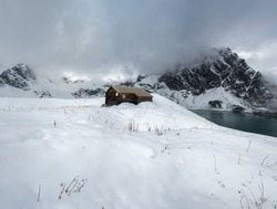 House in a snow-covered field against the background of mountains covered with fog and clouds