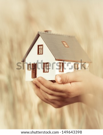 House in children`s hands against autumn yellow background. Real estate concept