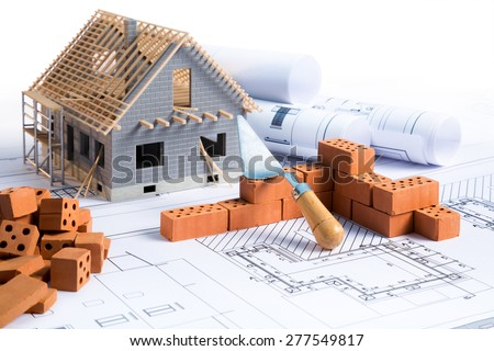 house in construction - project with brick and blueprint