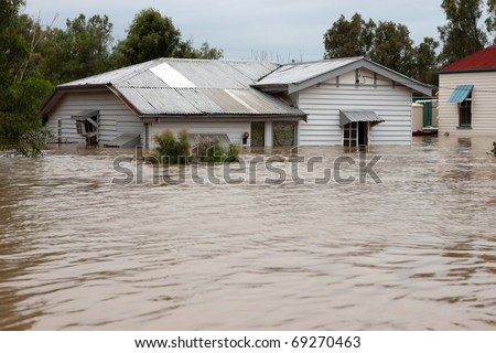 House in floodwater.  Traditional timber country home with water up the windows.  Ideal for insurance or disaster illustration.