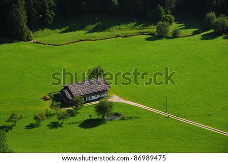 house in nature with plenty of green grass and forest