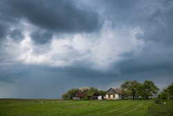 House in the field under storm clouds. Rural landscape.