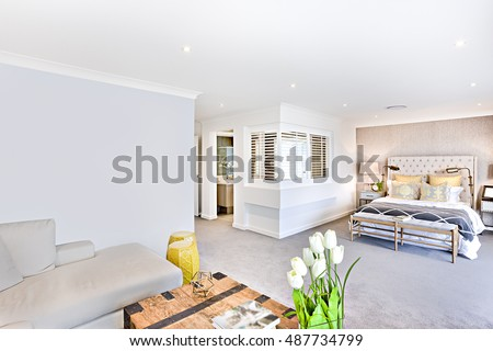 House interior with bedroom beside washroom and living area, including a carpeted hallway through the house and under the ceiling lights, cushion, sofa with white flowers in front of bed pillows