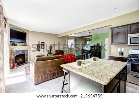 House interior with open floor plan. View of kitchen island with granite top and living room with fireplace #215654755