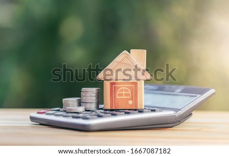 House is placed on the calculator and coin is on the calculator. planning savings money of coins to buy a home concept for property ladder, mortgage and real estate investment saving for a buy house.