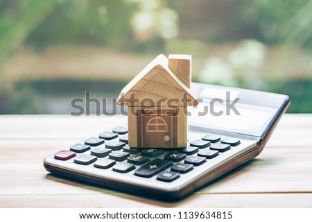 House is placed on the calculator. Imagine calculating to buy a home. planning savings money of coins to buy a home concept for property, mortgage and real estate investment.to buy a house.