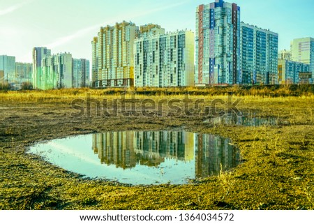 House is reflected on puddle. State of nature. wet land with puddles that reflect the buildings  #1364034572