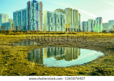 House is reflected on puddle. State of nature. wet land with puddles that reflect the buildings  #1365876407