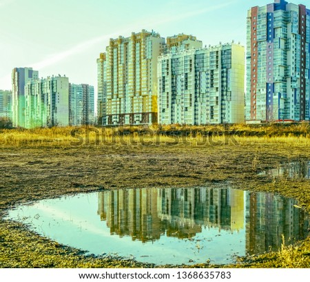 House is reflected on puddle. State of nature. wet land with puddles that reflect the buildings  #1368635783