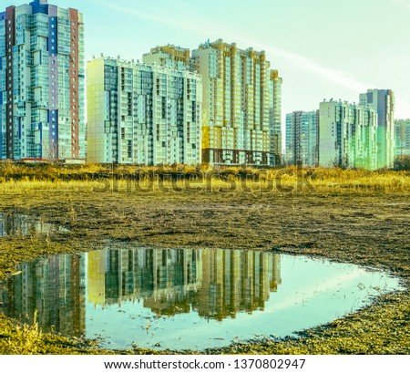 House is reflected on puddle. State of nature. wet land with puddles that reflect the buildings  #1370802947