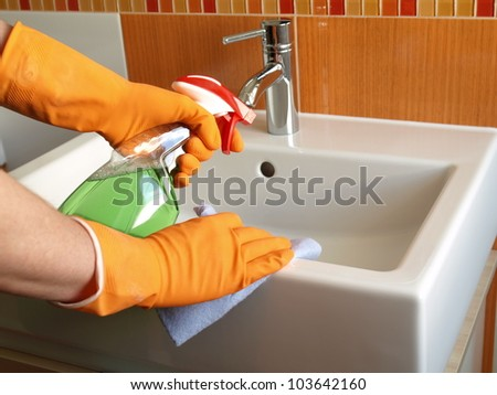 House keeping: cleaning bathroom sink with spray