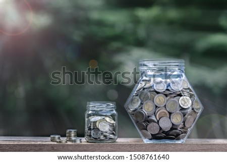House key and coin piles arrange into growth chart on white background, finance and business concept, copy space