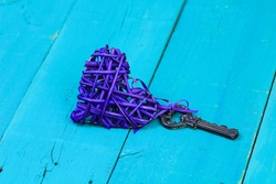 House key attached to purple wicker heart on antique rustic teal blue wood background; Valentines Day, home and love concept with painted copy space
