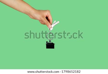 House key in woman hand. green background Stok fotoğraf ©