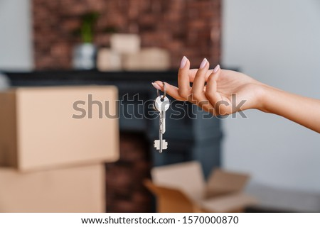 House key in womans hands, concept of moving or rent appartment