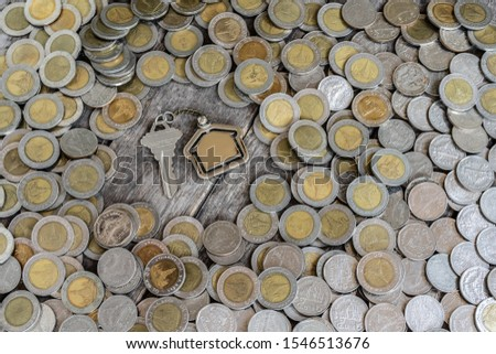 House key on coin stack background, business concept, copy space