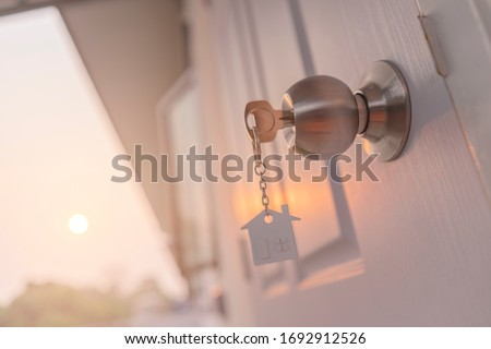 House key on house shaped keyring in the lock of door,Sunset background Foto stock ©