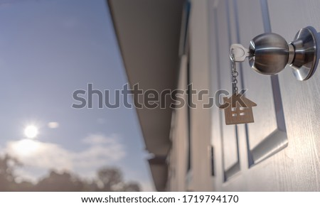 House key on house wood shaped keyring in the lock of the door, Sunlight background