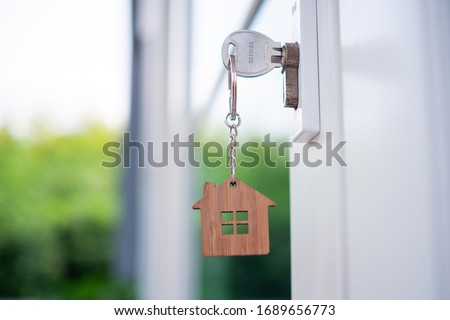 House key with a house key, made of wood in the keyhole ready to sell the concept of real estate.
