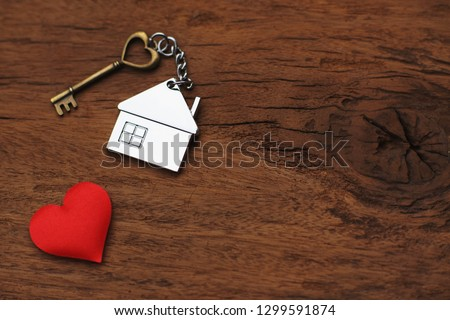 House key with home keyring decorated with mini red heart on wood texture background, sweet home concept, copy space