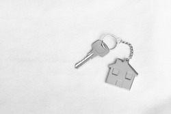 House key with home keyring in on white background, copy space
