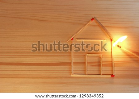 house laid with matches catching fire, arson, someone holding a burning match at the roof Stock photo ©