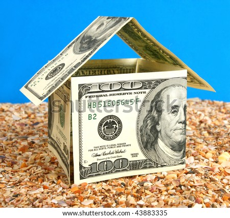 House made from 100 dollars on sand