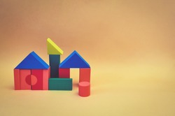 house made from wooden toy blocks on yellow background