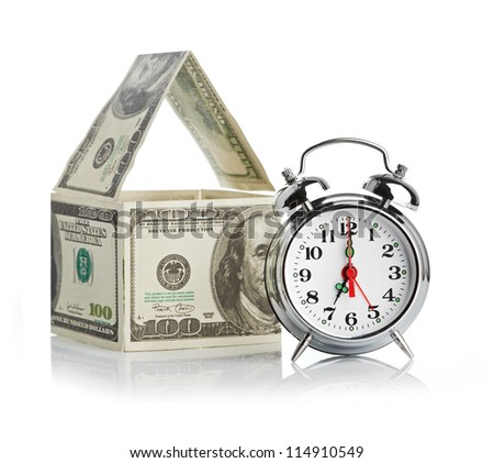 house made of dollars and alarm clock. Isolated on white background.