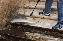 House maintenance : a manual worker cleans and defoams a dirty exterior stone staircase with the lance of a high-pressure washer, while the bad water, charged with moss, trikles down the steps