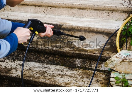 House maintenance : a manual worker cleans and defoams a dirty exterior stone staircase with the lance of a high-pressure washer, while the bad water, charged with moss, trikles down the steps Stock photo ©