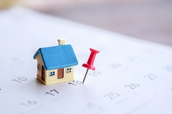 house model and red pin mark on calendar, due date for home payment ,property reminder concept