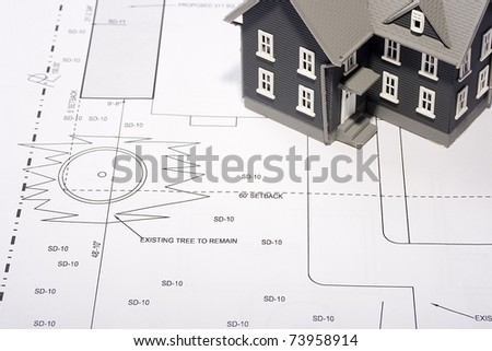 House model on a plan of a house construction.