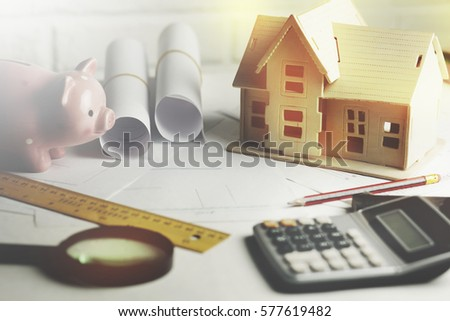 house model with calculator and piggy bank on table
