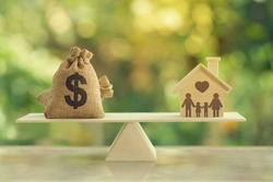 House mortgage and family financial management concept:  Wooden home and heart, Family member and US dollar hessian bags on balance scale. Prepare expenses for the purchase of a residence.