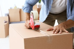 House moving concept. Closeup of man packing cardboard box