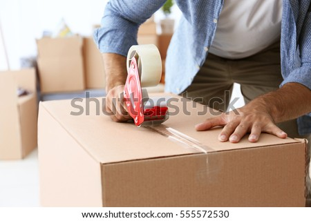 House moving concept. Closeup of man packing cardboard box #555572530