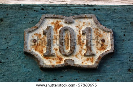 House number 101 An aging cast iron 'one hundred and one' on the outside of a building in the Vedado district of Havana, Cuba.