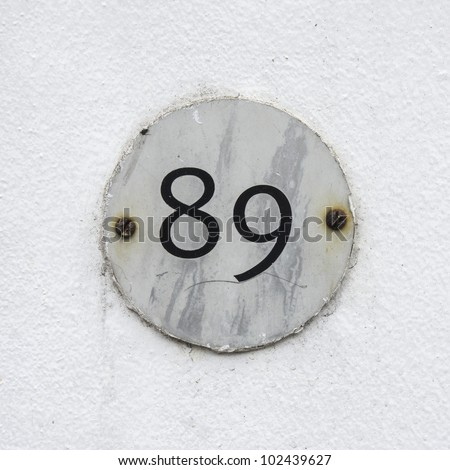 house number eighty nine on a small round plate attached with two rusty screws