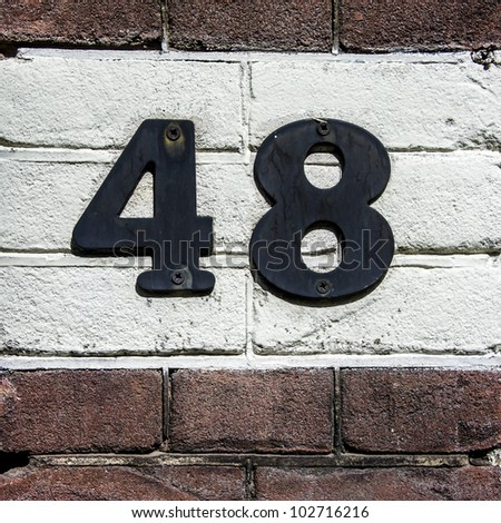House number forty eight. Black lettering on a white painted strip